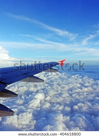 Airplane flying above the clouds, Aircraft wing over clouds - airtransport to travel. window view from airplane  - stock photo