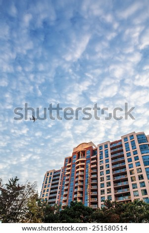 Airplane flying above the home building condo in city, white clouds in the sky, view from the ground - stock photo