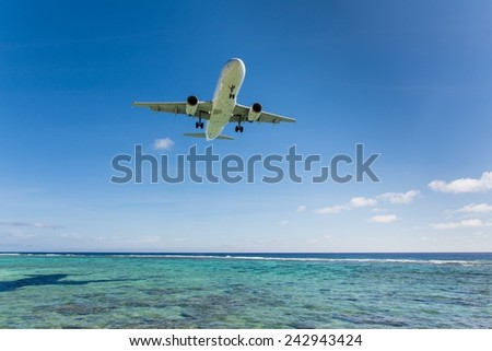 Airplane flying close over the blue ocean while landing on the Cook Islands - stock photo