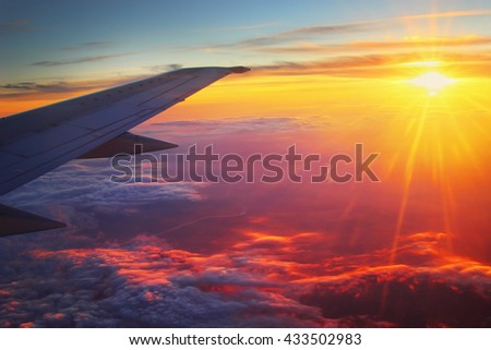 Airplane flying high above the clouds at sunset.