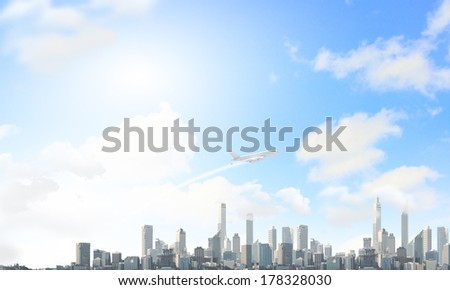 Airplane flying high in sky above city - stock photo