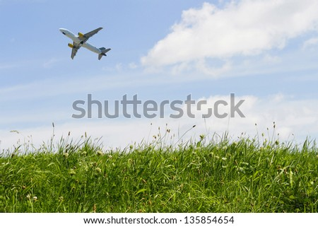 Airplane flying in a blue sky over green grass in summer - stock photo