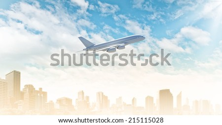 Airplane flying in blue sky above modern city