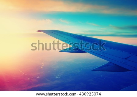 Airplane flying in the sky at sunset. Color filter applied. - stock photo