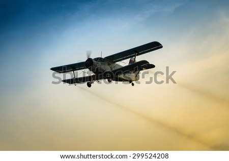 Airplane flying in the sky spraying mosquitoes - stock photo