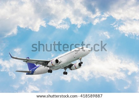Airplane flying on blurred blue sky and pattern of white cloud in evening light, Plane with sunlight, Plane in colorful sky or transport plane, Plane come down on the land