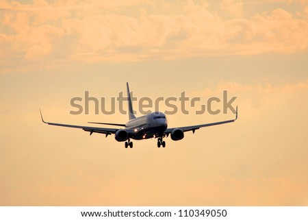Airplane flying on the sky at sunset