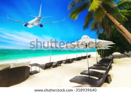 Airplane flying over amazing tropical beach with palm tree, white sand and turquoise ocean waves. Boracay island, Philippines vacation - stock photo