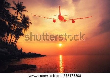 Airplane flying over amazing tropical sunset landscape. Thailand travel destinations   - stock photo