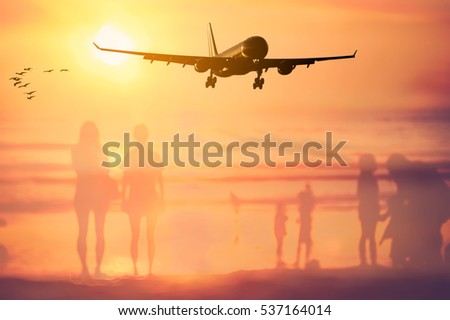 Airplane flying over blur people relax on tropical sunset beach with bokeh sun light wave abstract background. Copy space of summer vacation and business travel concept. Vintage tone filter color.