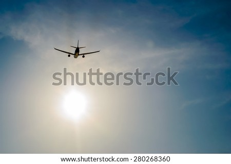 airplane flying over the sky and sun rays background ,Shot from the bottom - stock photo