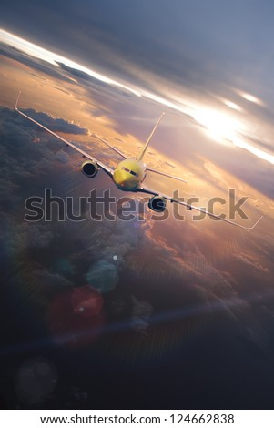 airplane flying through beautiful clouds at the sunset time with sunlight - stock photo