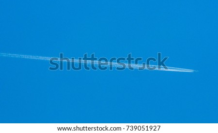 Airplane flying through blue sky with vapor trails