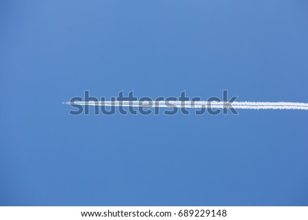 Airplane flying through clear blue sky leaving a vapor trail.