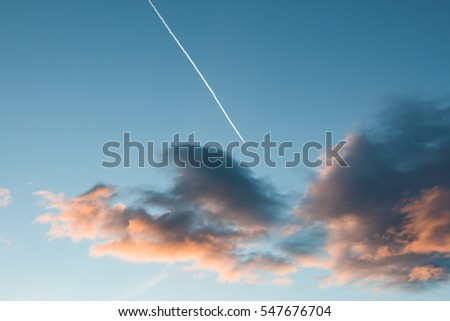 Airplane flying through sunrise clouds