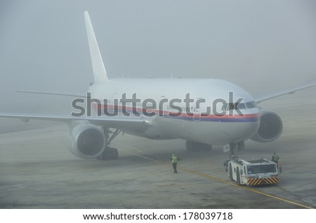 Airplane getting ready on a foggy day - stock photo