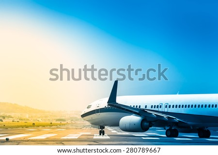 Airplane goes at taxiway to the position for takeoff at an airport runway at bright colorful sunrise morning/Plane Rolling to Take Off