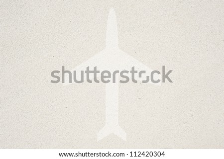 Airplane icon on sand background and textured