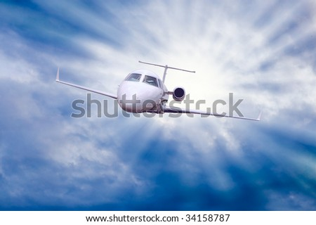airplane in air on blue sky with sun - stock photo