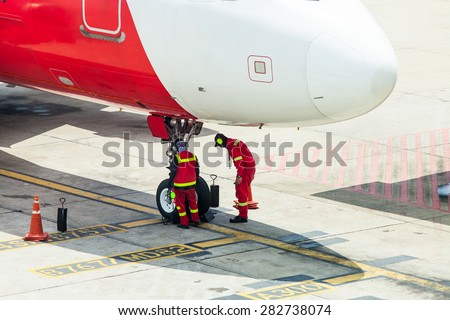 Airplane in airport serviced by the ground crew before departure at Don Mueang international Airport THailand - stock photo