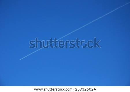 Airplane in Blue Sky with Condensation Trail  - stock photo
