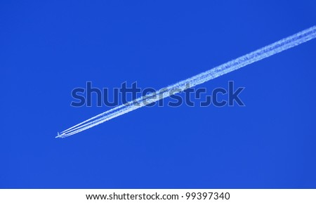 Airplane in Blue Sky with Condensation (Vapor) Trail - stock photo