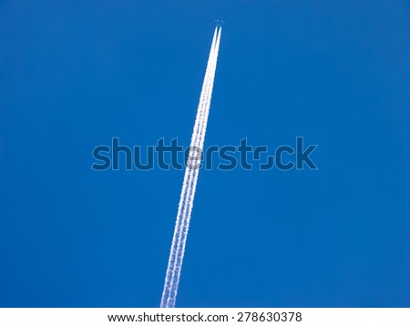 Airplane in blue sky with jet trail backgeound