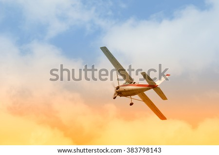 Airplane in flight with cloudy sky at sunset in summer