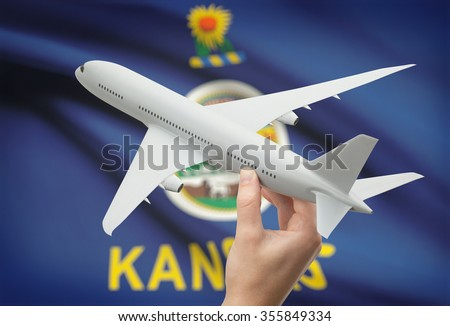 Airplane in hand with local US state flag on background - Kansas - stock photo