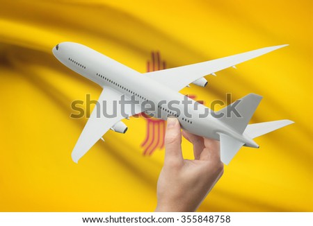 Airplane in hand with local US state flag on background - New Mexico - stock photo
