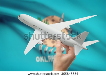 Airplane in hand with local US state flag on background - Oklahoma - stock photo