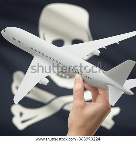 Airplane in hand with local US state flag on background series - Jolly Roger - symbol of piracy - stock photo