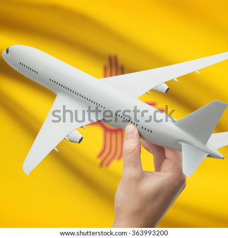 Airplane in hand with local US state flag on background series - New Mexico - stock photo