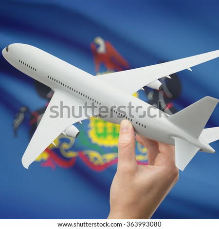 Airplane in hand with local US state flag on background series - Pennsylvania