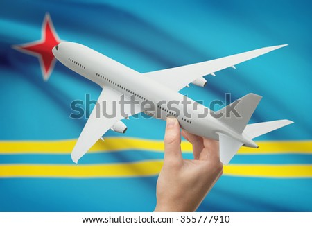 Airplane in hand with national flag on background - Aruba - stock photo