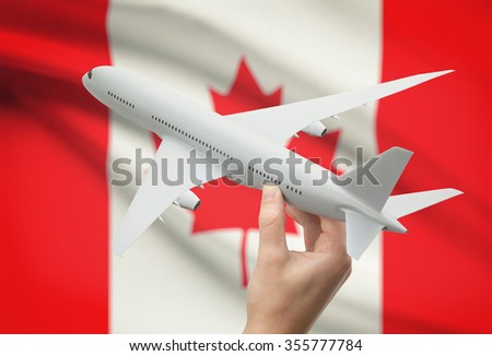 Airplane in hand with national flag on background - Canada - stock photo