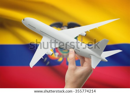 Airplane in hand with national flag on background - Ecuador - stock photo