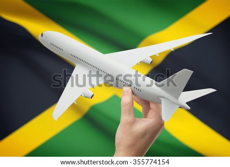 Airplane in hand with national flag on background - Jamaica - stock photo