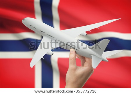 Airplane in hand with national flag on background - Norway - stock photo