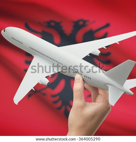 Airplane in hand with national flag on background series - Albania - stock photo