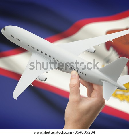 Airplane in hand with national flag on background series - American Samoa - stock photo