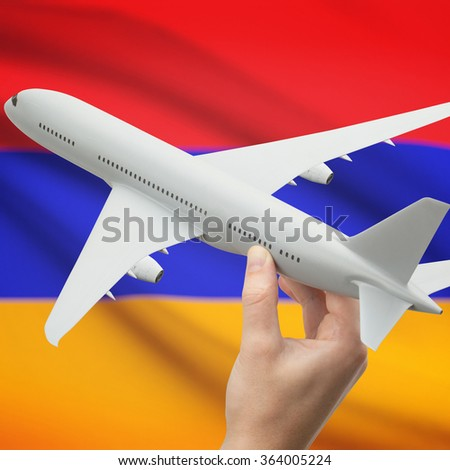 Airplane in hand with national flag on background series - Armenia - stock photo