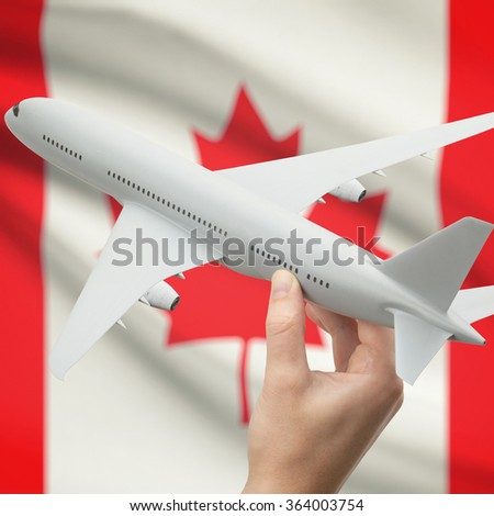 Airplane in hand with national flag on background series - Canada - stock photo