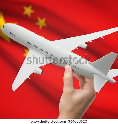 Airplane in hand with national flag on background series - China - stock photo