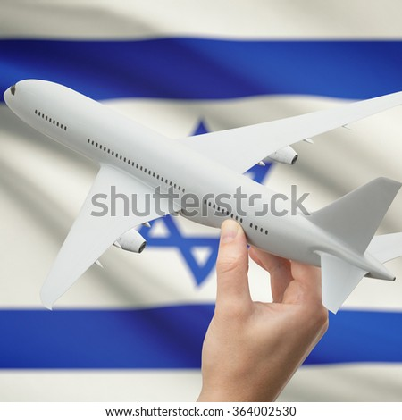 Airplane in hand with national flag on background series - Israel - stock photo