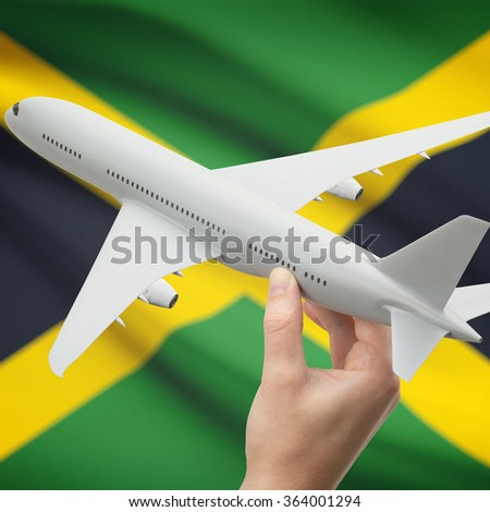 Airplane in hand with national flag on background series - Jamaica - stock photo