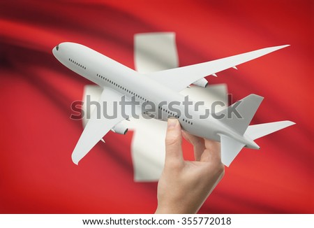 Airplane in hand with national flag on background - Switzerland - stock photo