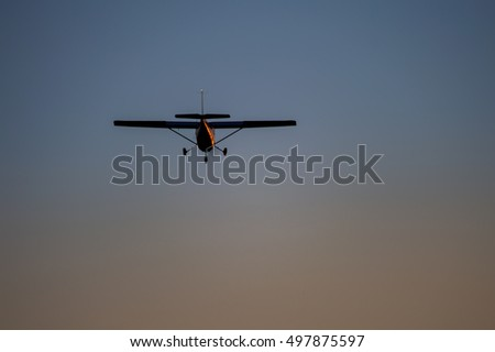Airplane in the air and sunset sky in background