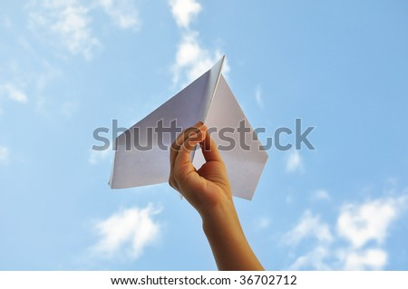 Airplane in the hand of child against the sky - stock photo