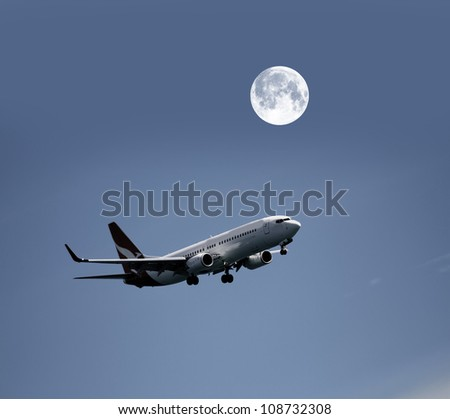 Airplane in the night sky and moon - stock photo
